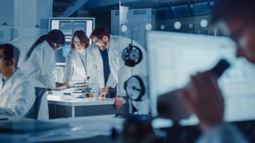 Dans un laboratoire de recherche technologique: une équipe diversifiée de scientifiques industriels, d'ingénieurs et de développeurs travaillent avec un tableau blanc numérique montrant les plans d'un moteur